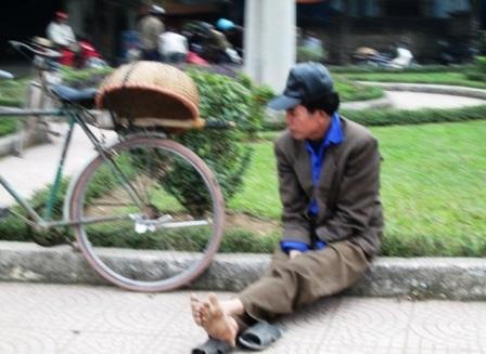 Người đàn ông co ro trong giá lạnh ngồi chờ việc.