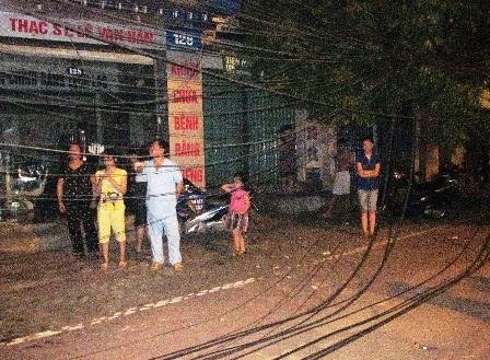 Tại hiện trường, dây điện bị đứt rơi xuống đường, nhiều người dân vẫn còn lo lắng.
