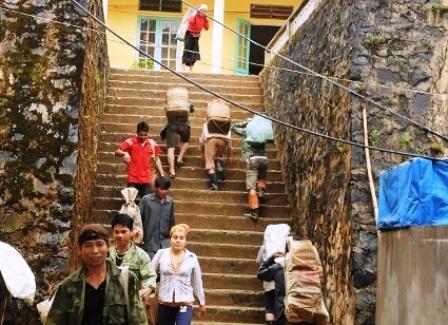 Người dân gùi vật liệu qua cổng trường cao hơn 5m…