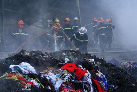 Lính cứu hỏa phải bới từng đống vải vụn để phun nước vào dập lửa