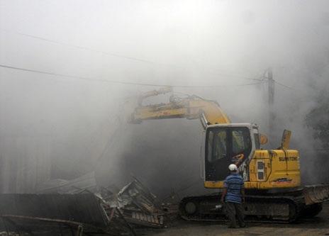 Xe cuốc được điều đến bới các đống hàng ra để dập tàn lửa âm ỉ bên trong