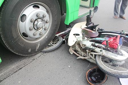 Đầu chiếc xe máy của nạnnhân nằm kẹt dưới bánh xe xe buýt
