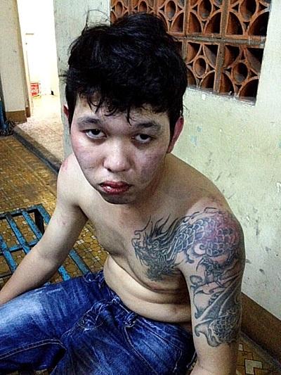 Nguyễn Phú Quý với hình xăm con rồng quấn quanh vai, bị bắt tại cơ quan công an