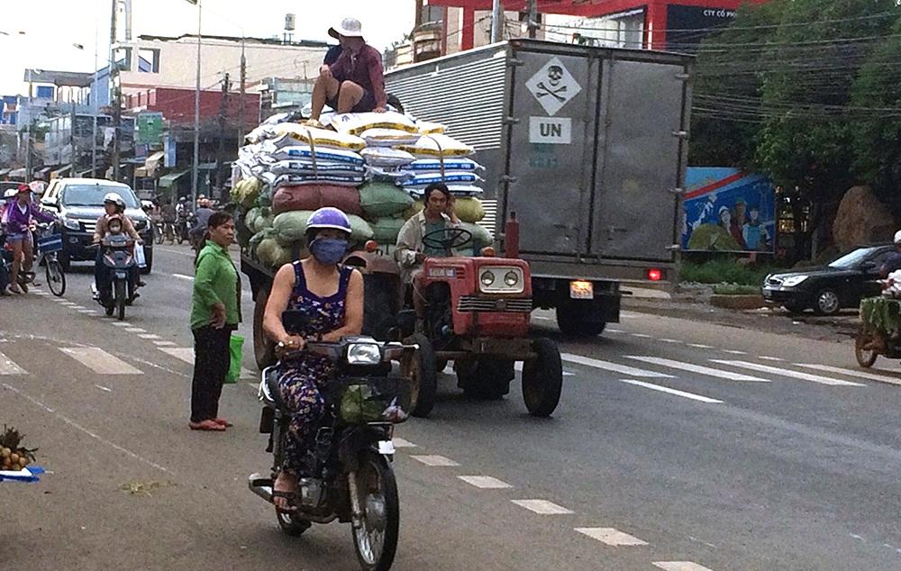 Xe máy cày tự chế chở hàng cồng kềnh và người ngồi vắt vẻo trên thùng hàng trên quốc lộ 20