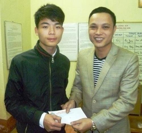 Anh Nguyễn Minh Hoàng (trái) được công ty điện máy trao thưởng 500.000 đồng
