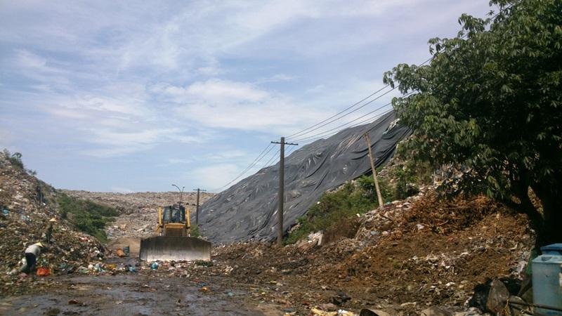 Núi rác khổng lồ chỉ được che sơ sài bằng một tấm bạt để rác không tràn ra phía sau