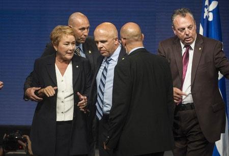 Bà Pauline Marois được hộ tống ra khỏi bục phát biểu khi tiếng súng vang lên.