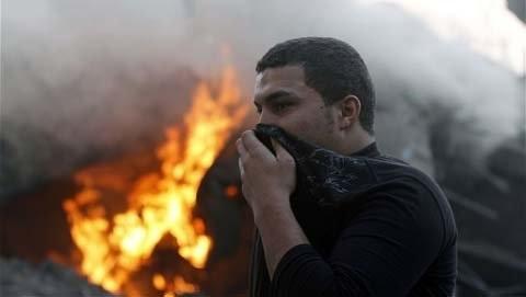 Một người đàn ông che mũi tránh khói sau một cuộc không kích của Israel ở Gaza City.