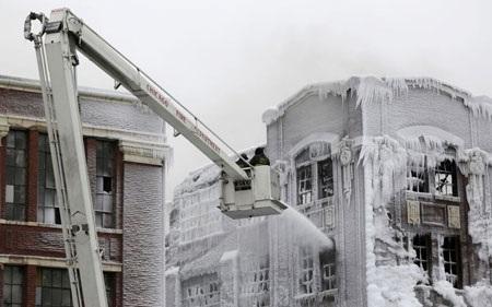 Lính cứu hỏa tiếp tục vật lộn với hỏa hoạn bên trong nhà kho trong khi mặt ngoài đã bị đóng băng.