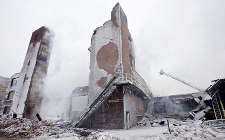 Lính cứu hỏa phun nước vào các điểm nóng của tòa nhà bị đóng băng.