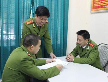 Trung tá Hòa (người đứng) trao đổi kết quả giám định cùng với các đồng đội