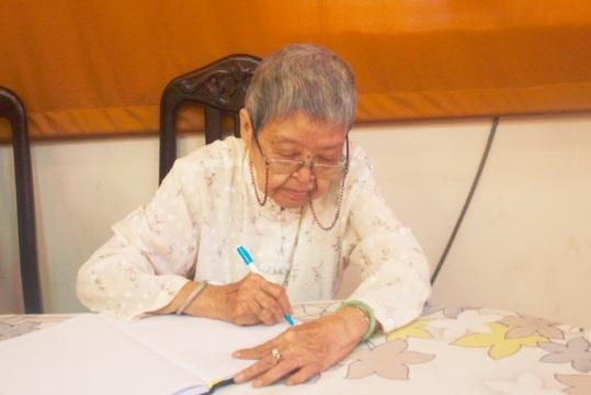 Cụ bà năm nay đã 90 nhưng bà vẫn tự tay mình ghi sổ tang bằng bàn tay run run.