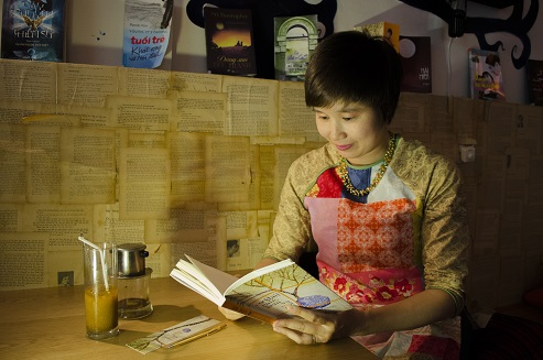 Nhà văn Hòa Bình bên trong không gian cà phê sách của chính mình bày trí.