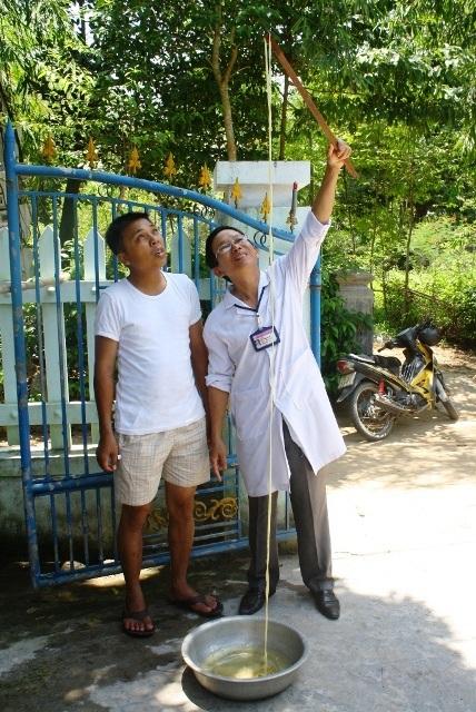 Y sĩ Lê Công Danh (phải) đang kiểm tra con sán