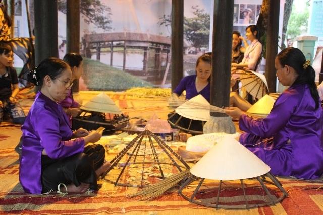 Các nghệ nhân làng nón Thanh Thủy đang trình diễn nghệ thuật làm nón lá