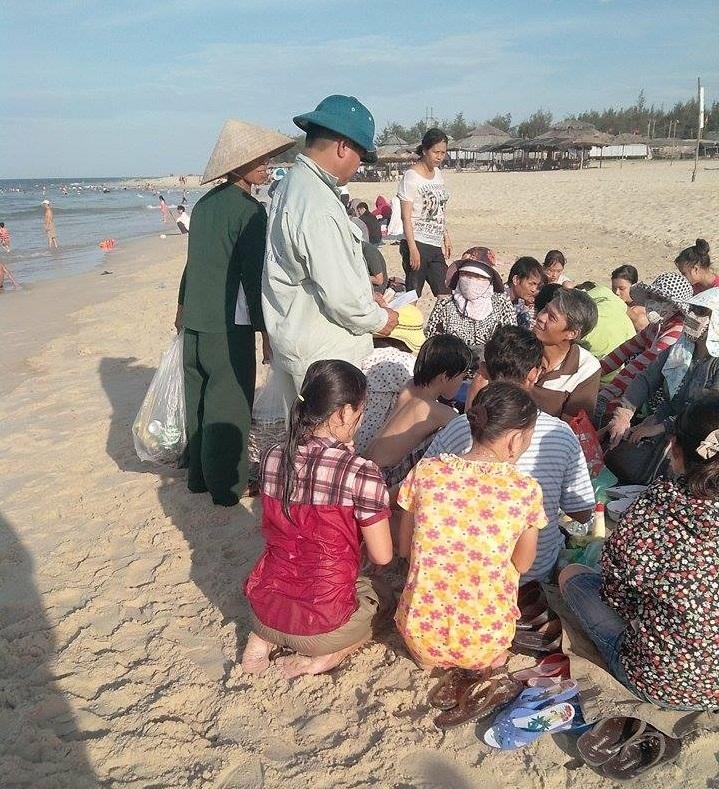 Một nhân viên môi trường đang đi thu phí nhóm khách ngồi chơi, ăn uống trên bãi biển Thuận An