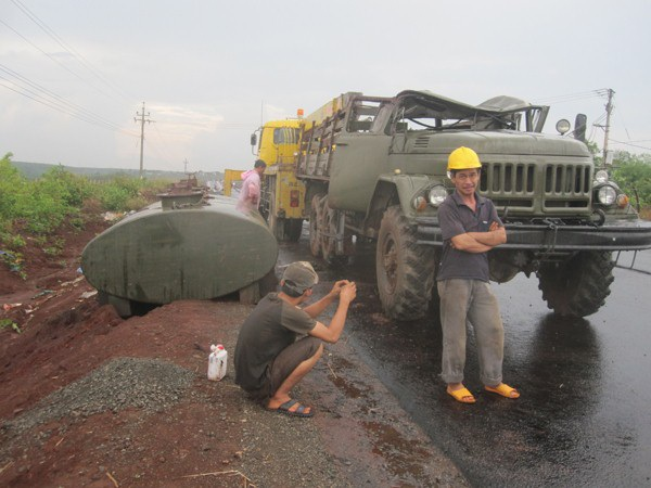 Cách đó không xa một chiếc xe chở xăng cũng đã bị lật xuống lề đường.
