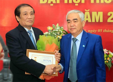 Ông Lê Hùng Dũng tặng hoa và kỷ niệm chương cho nguyên VFF Chủ tịch Nguyễn Trọng Hỷ - Ảnh: Gia Hưng