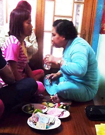 Bà Tám Cô đang chữa bệnh bằng cách dán bùa, dùng kim châm và phun nước lã vào người bệnh.
