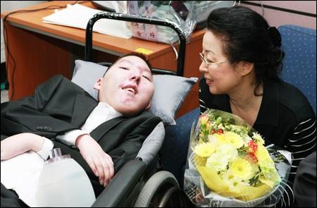 Cảm động tấm lòng của bà mẹ chàng sinh viên khuyết tật  - 1