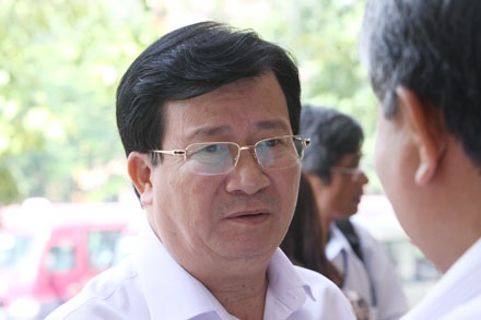 Bộ trưởng Trịnh Đình Dũng đang trao đổi với đại biểu bên hành lang hội trường (ảnh: Việt Hưng).