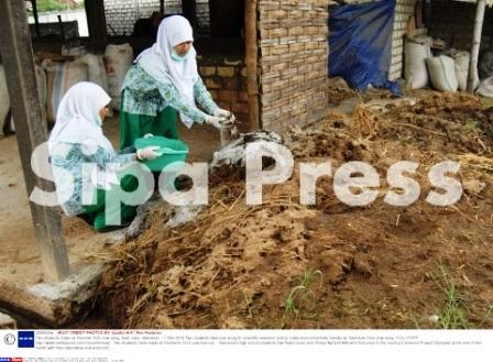 Dwi Nailul Izzah và Rintya Aprianti Miki lấy phân bòtại một trang trại ở phía Đông đảo Java