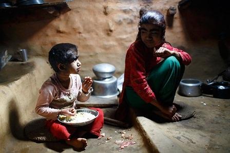 Manjura ngồi cạnh em gái của mình trong lúc ăn cơm trưa tại nhà
