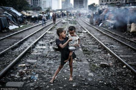 Hình ảnh 2 em bé đang ăn những thức ăn bỏ đi bên cạnh đường tàu ở