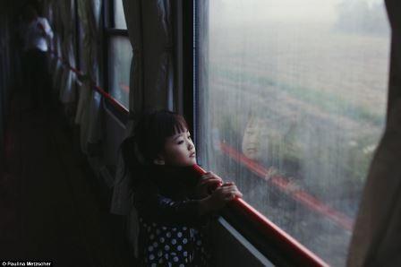 Hình ảnh một em bé nhìn ra ngoài cửa kính ngắm mưa được chụp ở Đức bởi tác giả