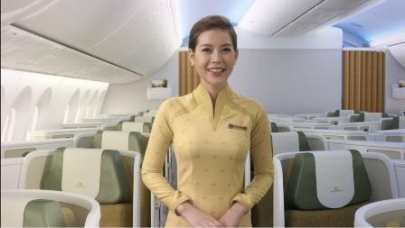 Tiếp viên phục vụ khoang khách hạng thương gia mặc áo dài màu vàng nhẹ