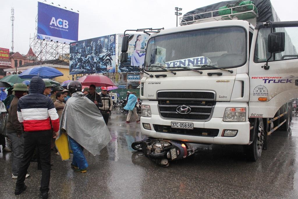 Chiếc xe máy nằm dưới đầu xe tải.