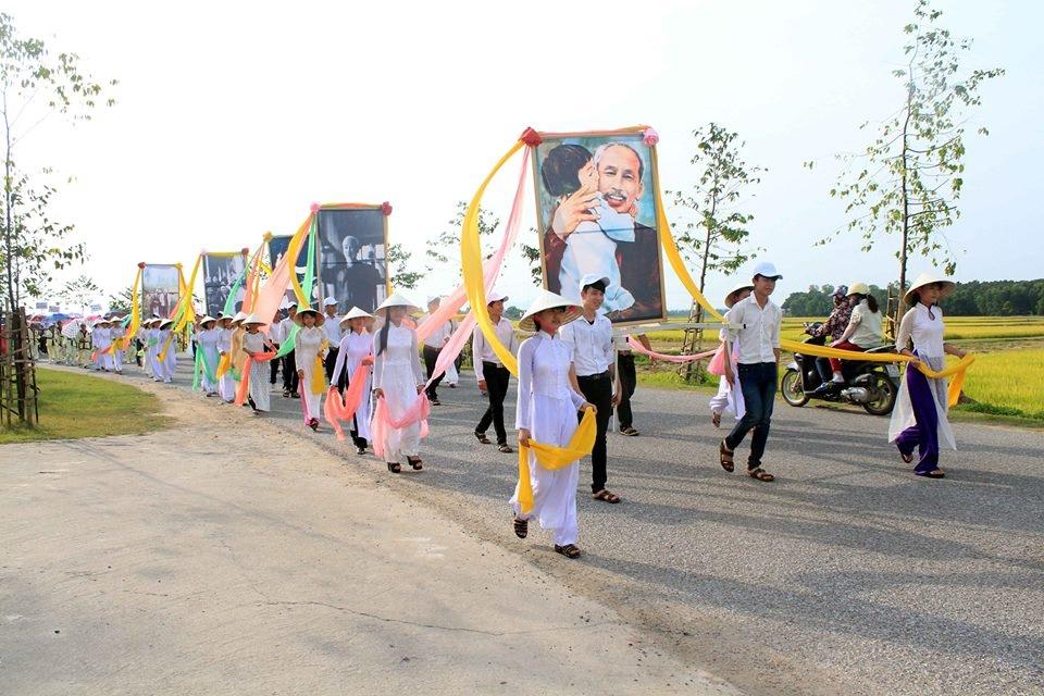 Đôi TNTP dẫn đầu đoàn rước với bức chân dung của Bác.