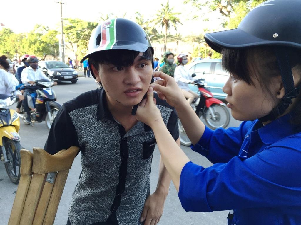 Sinh viên tình nguyện giúp đỡ Tuấn cài quai mũ bảo hiểm để về phòng trọ.