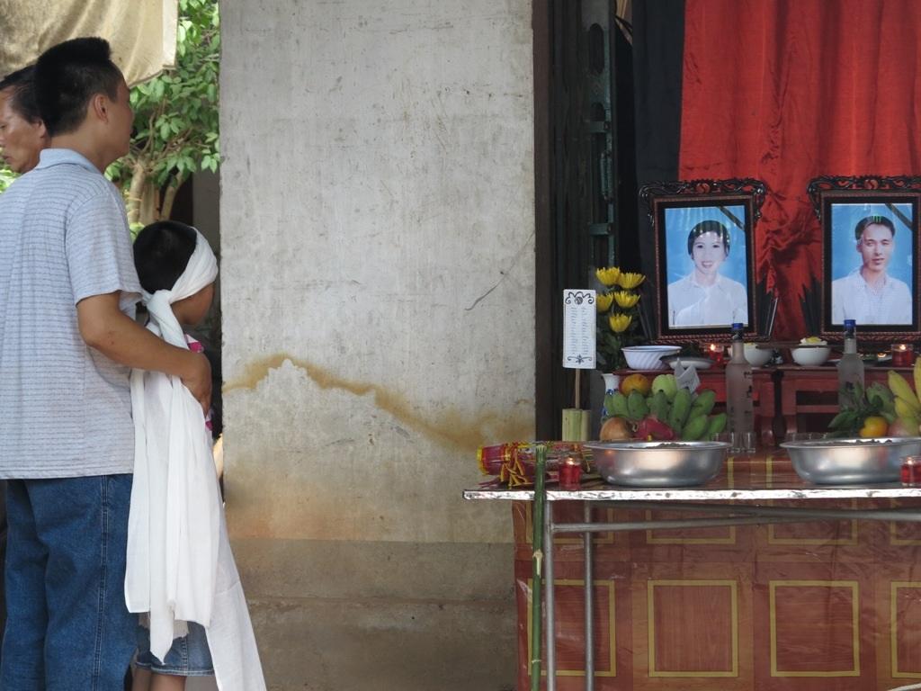 Đứa con trai đầu ngơ ngác nhìn lên bàn thờ của bố mẹ.