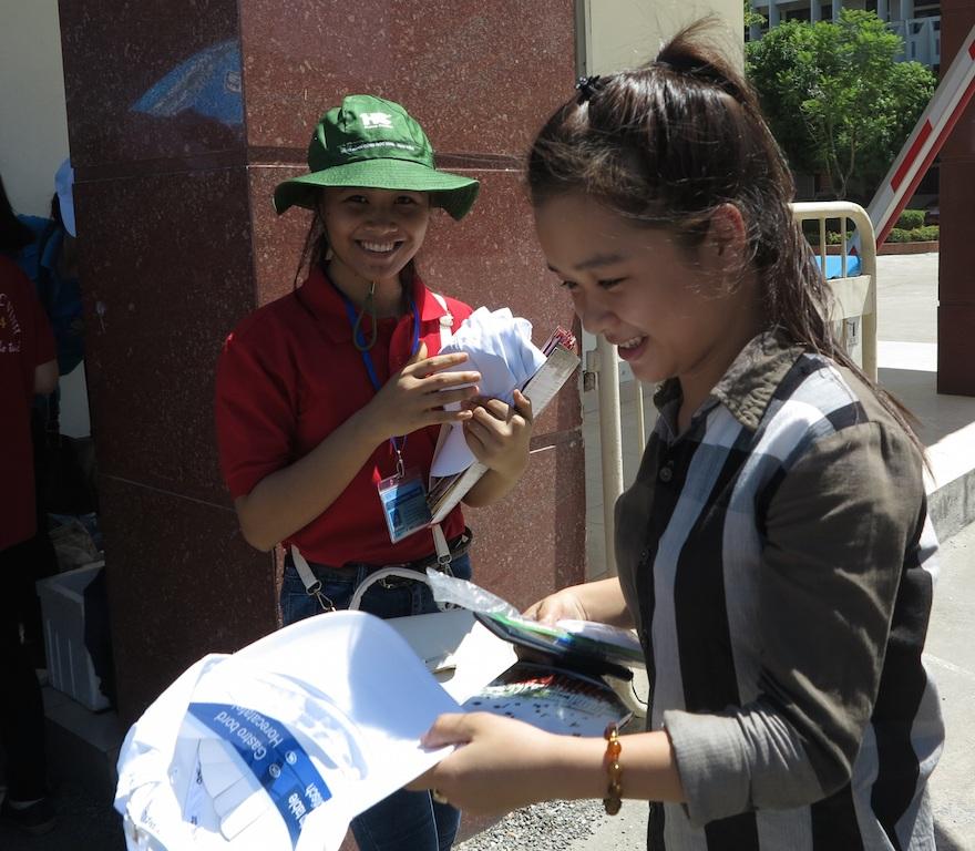 Thí sinh cụm thi Vinh vừa ra khỏi địa điểm thi được phát mũ miễn phí đội chống nắng.
