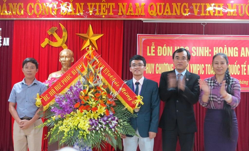 Lãnh đạo UBND tỉnh Nghệ An tặng hoa chúc mừng cậu học trò giành HCB sau 18 năm chờ đợi.