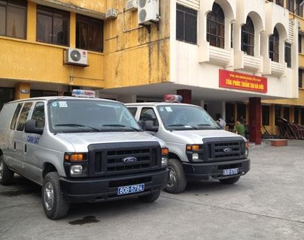 Những chiếc xe thùng chở các bị cáo đến tòa.
