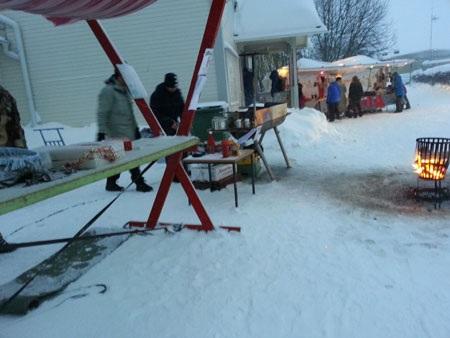 Một vài gian hàng nhỏ bày bán thức ăn đặt bên ngoài. Một bếp lửa đỏ rực đã làm tan giá ở góc chợ