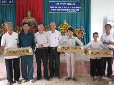 Nhà báo Nguyễn Quốc Khanh (thứ 3 từ trái sang) trao tặng gà cho bà con xã Bùi Xá