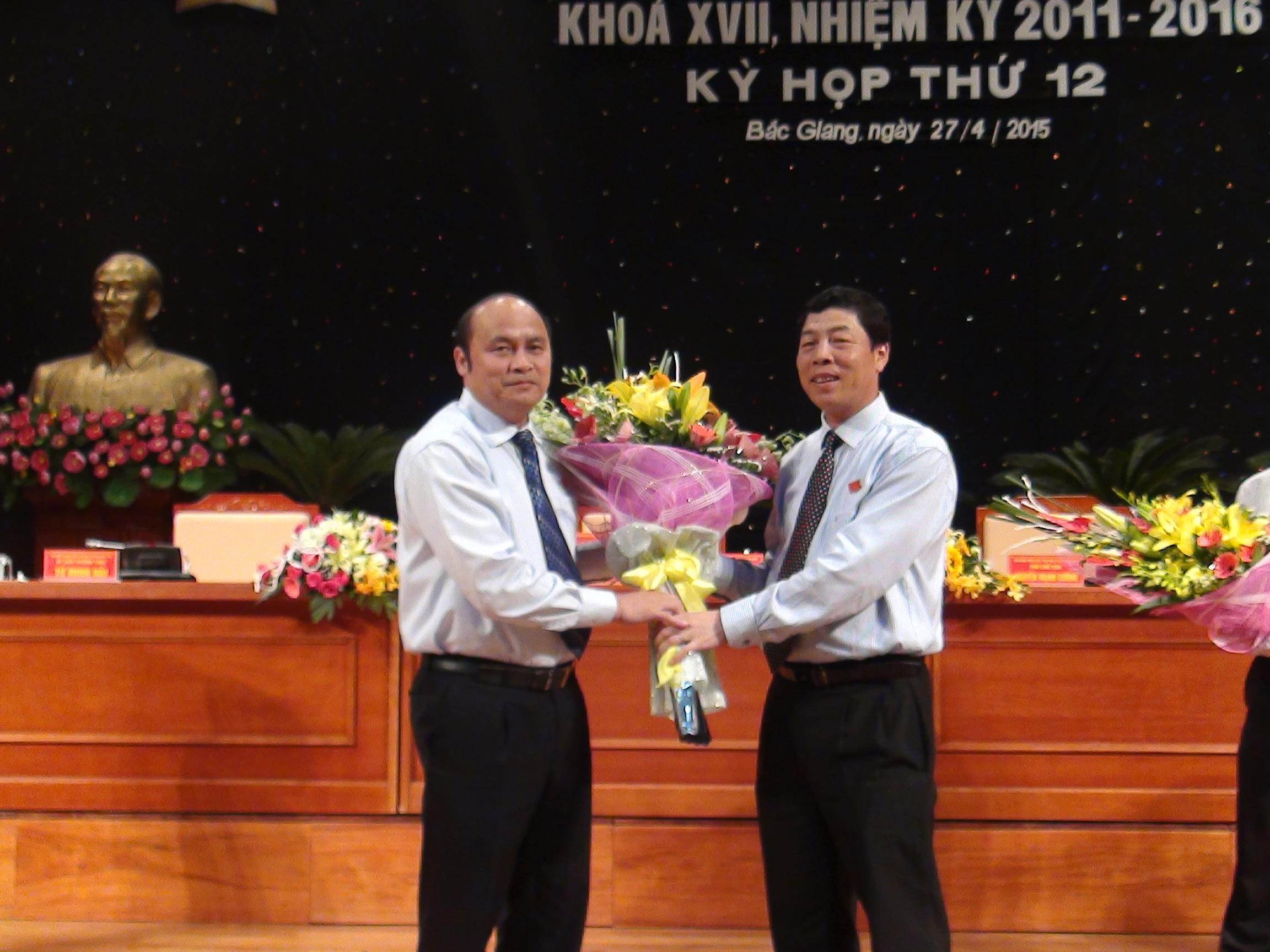 Bí thư Tỉnh uỷ Bắc Giang Bùi Văn Hải tặng hoa chúc mừng tân Chủ tịch UBND tỉnh Nguyễn Văn Linh.