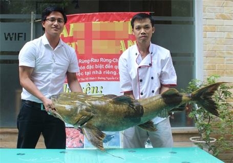 Anh Thọ (bía trái) phấn khởi mua được con cá Chiên quý, hiếm
