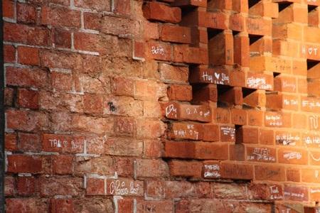 Một vài viên gạch đã bong tróc, tường bị bôi bẩn đầy các ký tự. Ảnh: Lê Phong