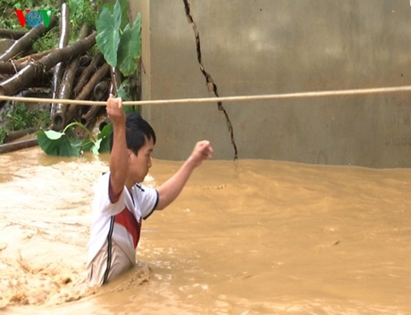Người dân phải đu dây vượt nước lũ để vào nhà