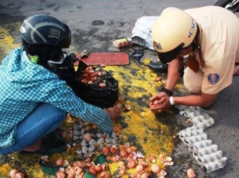 Hình ảnh hai chiến sĩ dùng tay hốt trứng vỡ cho vào túi ni lông giúp chị Mai trên đường.