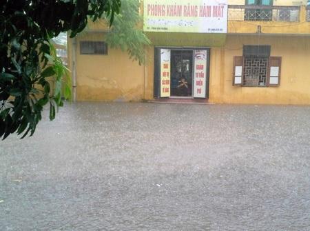 Nước mưa mấp mé cửa dù nhà đã đôn cao cả mét so với mặt đường (ảnh bạn đọc Kiều Thu cung cấp).