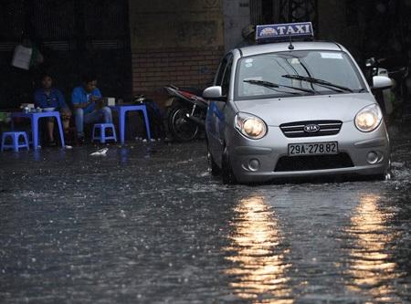 Vỉa hè cũng ngập nước, taxi phải bật đèn pha trên đường.