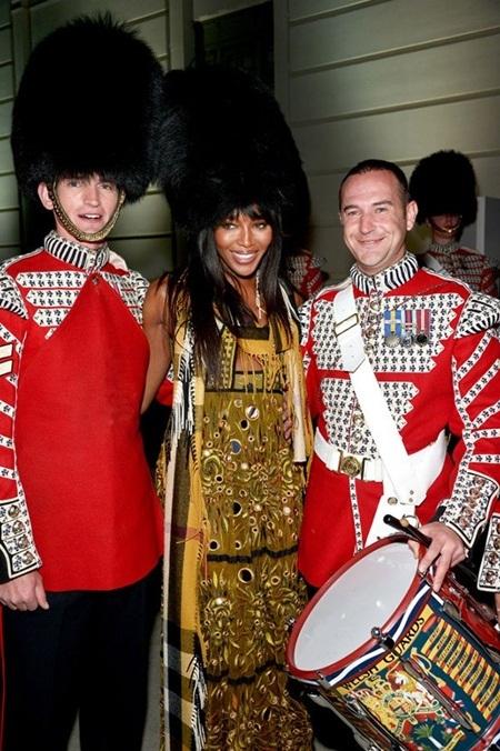 Naomi Campbell (giữa) tạo dáng với hai người lính trong đội quân nhạc Hoàng gia Anh