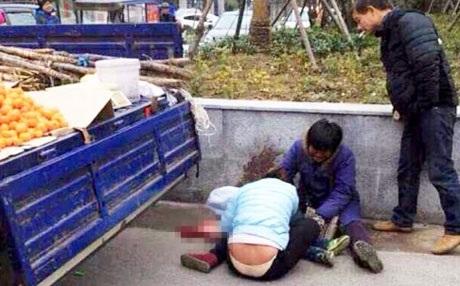 Hai vợ chồng người bán hoa quả đang ôm con khóc trên đường phố Hàng Châu. (Ảnh: SCMP)