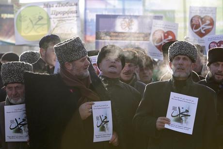 Người biểu tình mặc trang phục truyền thống cầm biểu ngữ phản đối