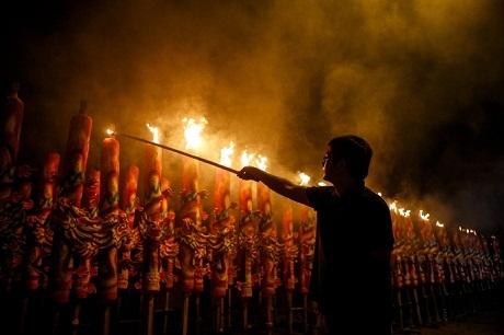 Một người đàn ông đốt những nén hương khổng lồ trong dịp năm mới tại chùa